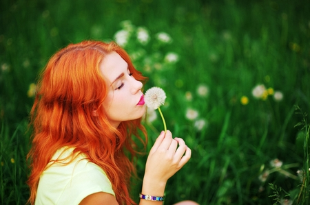 Beautiful young woman with closed eyes smelling a flower on a blurred background of green grass in summer Park. Close-up Standard-Bild