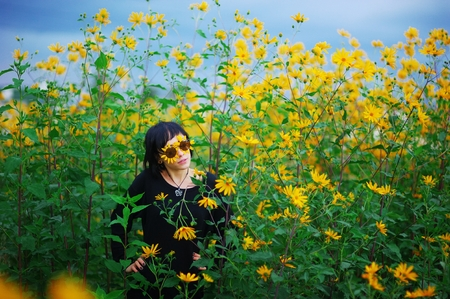 Portrait of a young girl brunette in sunglasses, decorated with yellow flowers posing among dense Jerusalem artichokes in a Sunny summer day during a country walk
