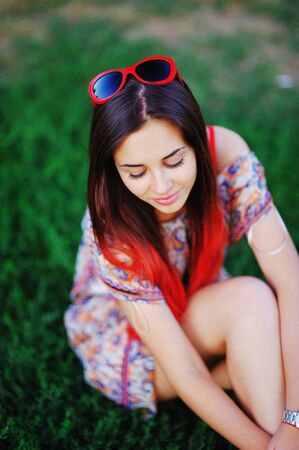 Beautiful portrait of adorable modest smiling girl with closed eyes, painted with red ends of long hair sitting on the grass in the forest on blurred background, close-up. Stock Photo