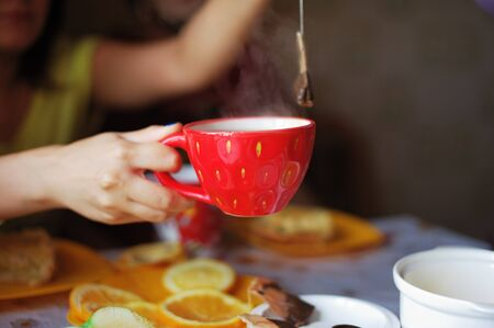 Female hands holding red Cup of hot tea and a tea bag over the table with food, blurred background.