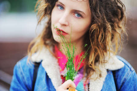 Young pretty girl with dreads with a bouquet of herbs in hand on a blurred background, closeup.