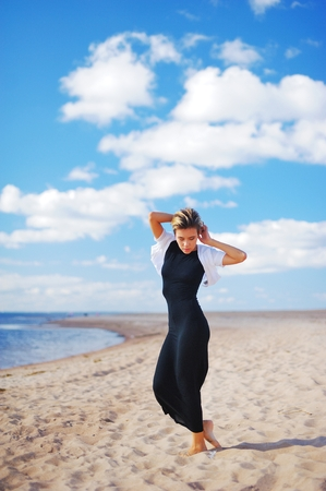 blue background: Young slim pretty women posing barefoot on the sandy shores on background beautiful white clouds on blue sky.