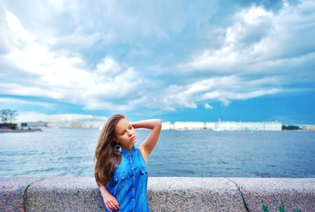 The pensive long-haired young girl in a denim shirt is standing on the bridge and straightens hair on blurred background of the river and a blue sky summer day.