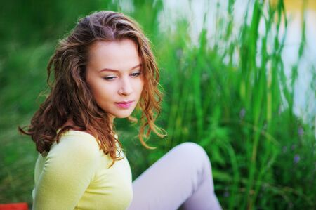 Portrait of beautiful caucasian girl with curly hair sitting on a green lawn near the river with downcast eyes, close-up.