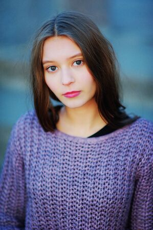 Portrait of young beautiful long-haired girl brunettes with attentive brown eyes in a knitted purple jumper in the open air on a blue blurred background, closeup