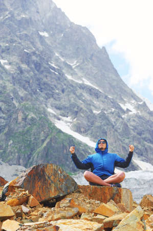 Young man in sunglasses and blue jacket with hood sitting on edge of cliff in pose of Lotus with their hands up, against background of snow-capped peaks. Sport and concept of a healthy lifestyle. Stock Photo