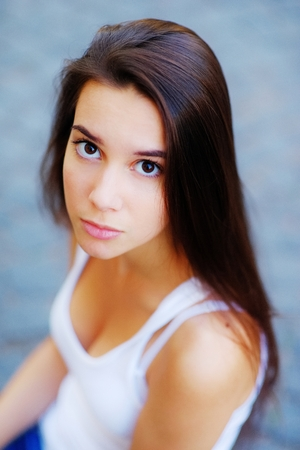 Portrait of young serious girls long-haired brunette with beautiful brown eyes in a white t-shirt outdoors on a gray-blue blurred background, closeup.
