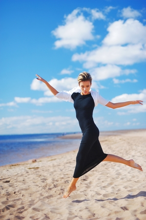 Wonderful portrait of young elegant woman in black dress with white Bolero, dancing barefoot on the sand, on a background of blue sky and white clouds of air.