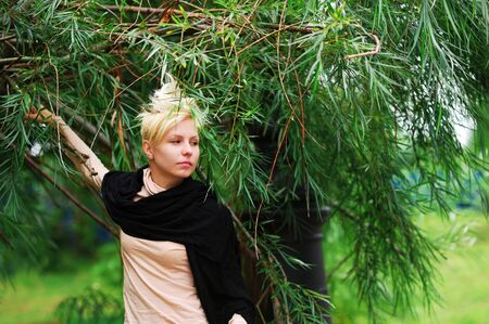 Young cute girl with blonde, tousled by the wind, the hair with a black tippet on their shoulders posing near a tree in summer Park.