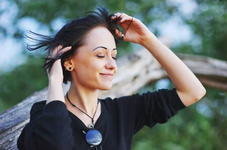 Portrait of shy beautiful woman with closed eyes and a sweet smile in the Park on a blurred background of green trees, close up.