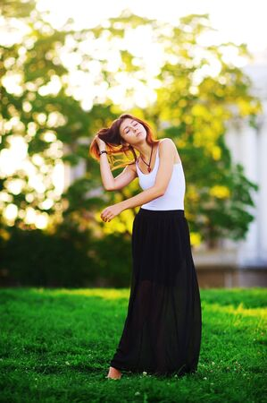 Portrait in full growth the beautiful long-haired women in white tank top and long black skirt in the Park. A young girl with eyes closed standing on a green grass and straightens hair.