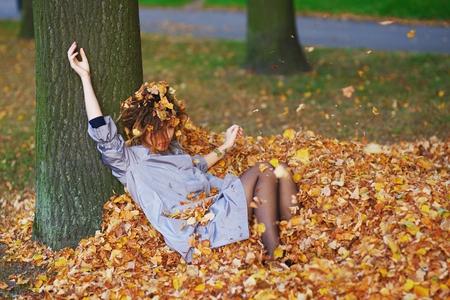 Nettes jugendlich Mädchen, das Blätter oben im Herbstpark wirft.