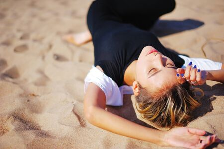 Young slim pretty girl in a black dress and white bolero with closed eyes resting on the sand under bright rays of sun, closeup