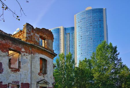 The old destroyed building against the backdrop of a new multi-storey skyscraper. Stock Photo
