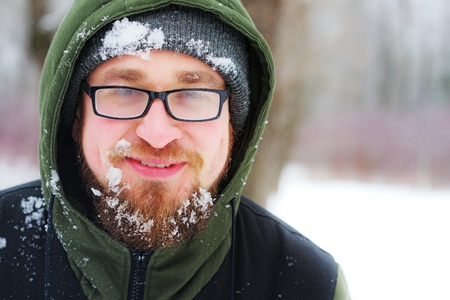 A bearded man with glasses, a hat and a hood in the snow. He smiles