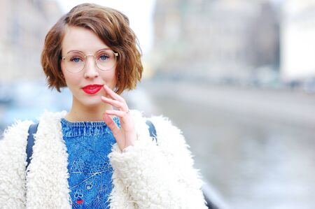 shortsighted: Portrait of young beautiful pensive woman in glasses on a city street in the blurry background. Close-up.