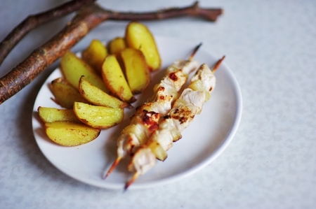 Delicious baked quartered potatoes with chicken kebabs on skewers on a white plate and on the table next branch for decoration, top view closeup. Stock Photo