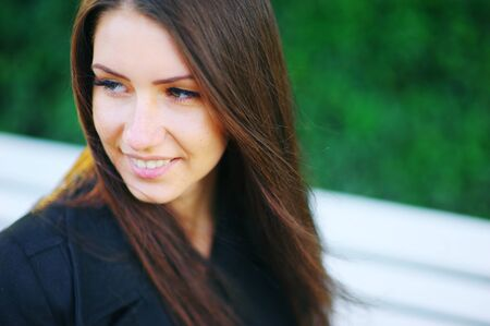 Portrait of a beautiful smiling Caucasian white girls on blurred green background. A woman of natural beauty with long hair, selective focus, close-up.