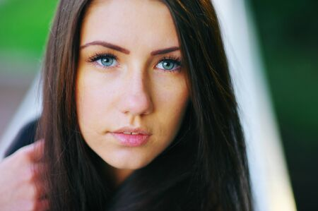 Gorgeous portrait of cute young long-haired girl with beautiful blue eyes closeup. Stock Photo