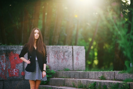 Portrait of a long haired pretty girl with the watch on the hand in a black jacket and short striped skirt posing on the stairs in the rays of light in summer green Park