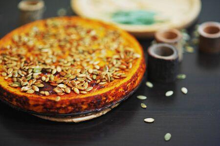 El pastel de calabaza delicioso, asperjado con las semillas en una tabla negra al lado de un tablero de madera salga las hojas, primer de la visión superior.
