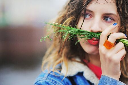 Young funny girl with dreadlocks poses a grimace, putting a tuft of grass on the lips, outdoors, close-up