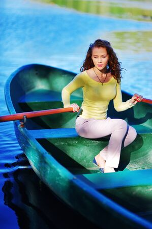 Sporty young beautiful lady rowing in wooden boat on water on a bright Sunny day. The concept of a healthy lifestyle.