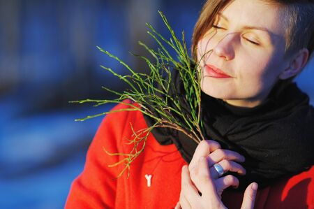 portrait of a happy young woman with eyes closed in a red coat with a green sprig in hand on a blurred background of a winter Park in the bright rays of the setting sun. Stock Photo
