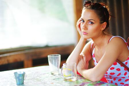 Cute young woman with beautiful brown eyes sitting at the table in cafe and thoughtfully looks into the camera. Portrait, closeup.