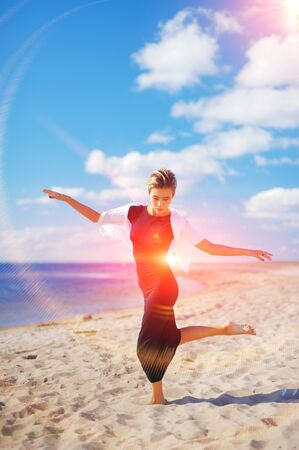 sun energy: Wonderful portrait of young elegant woman, dancing barefoot on the sand, on a background of blue sky and white clouds of air. Stock Photo