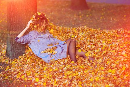 Cute teen girl throwing leaves up in the autumn park. Stock Photo