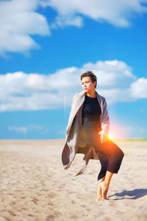 Young beautiful modern girl in a black dress and a light overcoat posing barefoot on a sandy beach on a Sunny day.