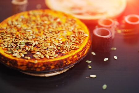 Ruddy pumpkin pie, topped with pumpkin seeds on the black table and sage leaves in Board , top view closeup.