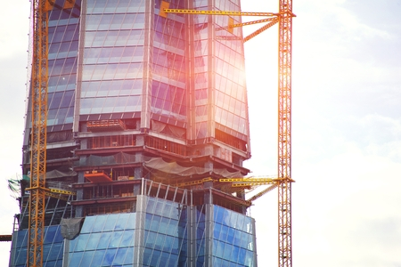 Construction of high-rise office center with modern technology. Fragment of a building on a light background of the sky. Close-up. Free place for text. Banco de Imagens