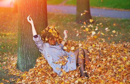 Pretty girl throws leaves in autumn park. Stock Photo