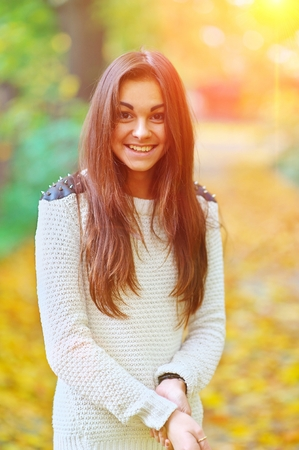 Portrait of young beautiful happy girls long-haired brunette with a truly sincere smile and mischievous brown eyes while walking in the autumn Park, blurred background, close-up. Stock Photo