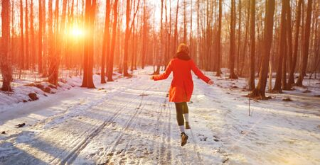 Young slender girl in a red coat runs along a snowy path in the Park, fun bouncing and waving his arms.