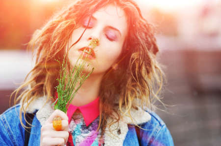 Young pretty girl with dreads with closed eyes and a tuft of grass in his hands outdoors on a bright day, close up Stock Photo