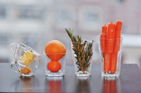 Nicely laid out set of products from carrots, rosemary, citrus, butter and honey in a glass container on the table on blurred background. Side view, close-up.