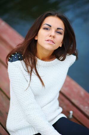 Portrait of beautiful confident girls with long hair in a white sweater with studs on shoulders, sitting on a wooden bridge, on blurred background of the river. Closeup. Stock fotó