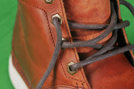 winter brown leather boots on a green background. Modern fashion and style. bootlace Closeup.