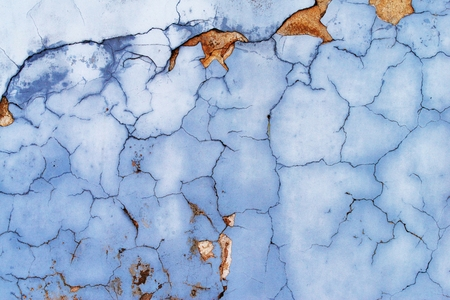 Aged street wall background, texture. The wall is painted with old blue cracked paint. An old concrete wall. Imagens