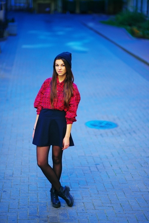 Portrait of a young beautiful long-haired girl in a cap, red checkered shirt, short skirt, black tights and boots on the sidewalk on the city street. The concept of youth street fashion. Stock Photo