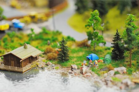 Miniature log house with tiled roof, near tiny figures of people sitting by the fire, near trees on blurred background