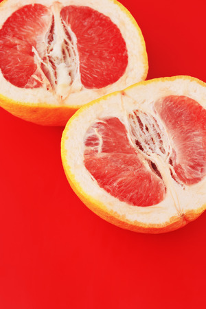 Two Red Grapefruit slices on red background. Minimal healthy fresh fruit concept. Fashion Top View.