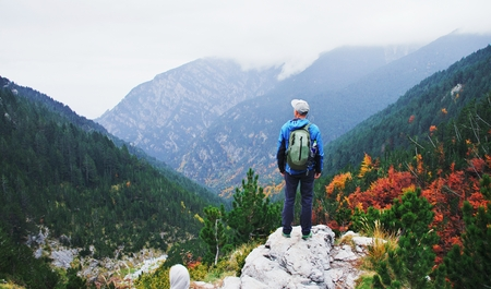 Man traveler hiking in mountains. Adventure solo traveling lifestyle. Wanderlust adventure concept. Active weekend vacations wild nature outdoor. Mount Olympus, Greece, europe, autumn fall, october. Stock Photo