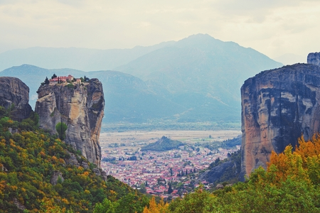 Monastery Meteora Greece. Stunning summer panoramic landscape. View at mountains and green forest against epic blue sky with clouds. Stock Photo