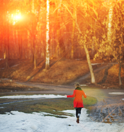Young girl in a red coat flees, waving his arms, on a snowy road in the Park Stockfoto