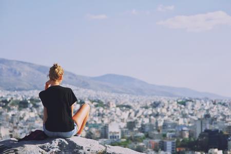 Jonge toeristische vrouw zittend op de top van de berg en kijken naar een prachtig landschap stadsgezicht Athene Griekenland. Volwassen meisje toeristische ontspannen op de heuvel met uitzicht op Athene in de zomer. Beroemde stad Athene in Europa