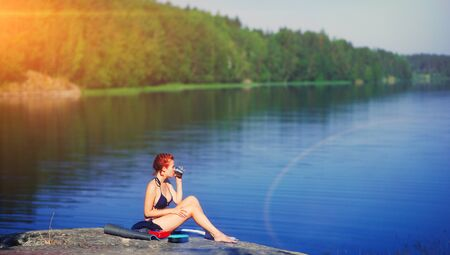 happy woman sitting drinks coffee with a view of lake landscape Young tourist woman drinks hot drink from cup and enjoy scenery sunrise. Travel tourism concept, happiness or inspiration concept, life